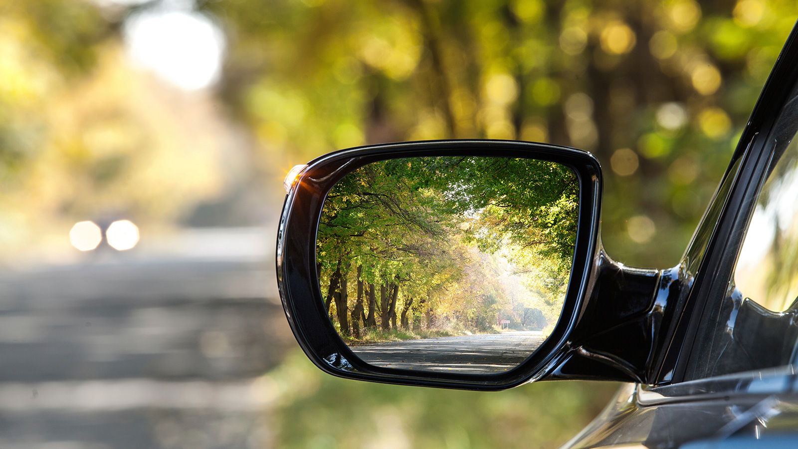 Reflection of a street in a rear view mirror during fall